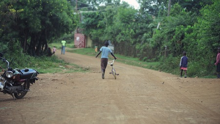 KENYA, KISUMU - MAY 20, 2017: Back view of boy walking through the road in Africa. Male with bicycle walking in forest.