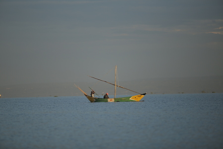 KENYA, KISUMU - MAY 20, 2017: Beautiful view of the sailboat in sea in Africa. Ship with people is going fishing. Calm landscape. Redakční