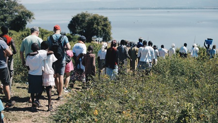 KENYA, KISUMU - MAY 20, 2017: Big group of African and Caucasian people are going together to the shore of the sea.