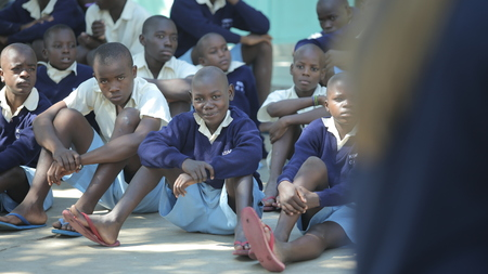 KENYA, KISUMU - MAY 20, 2017: Group of african children sitting on ground. Boys and girls in uniform spend time outside. Handsome boy smiling аn the camera