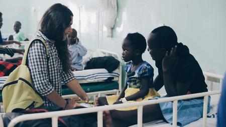 KENYA, KISUMU - 20 MAI 2017 : Groupe de personnes de race blanche tenant un petit enfant africain sur les mains. Volontaires à l'hôpital.