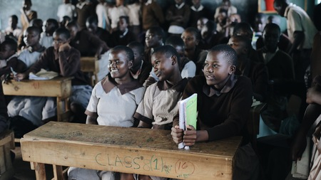 KENYA, KISUMU - MAY 20, 2017: Group of happy African children sitting in classroom and smiling, laughing together.