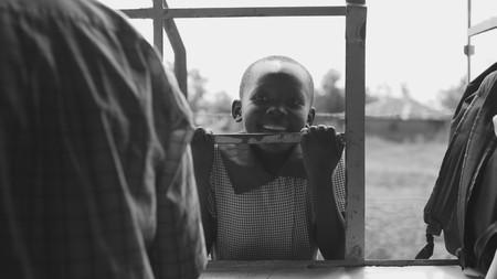 KENYA, KISUMU - MAY 20, 2017: Portrait of little african boy smiling, holding on lattice. Cute male spending time outside