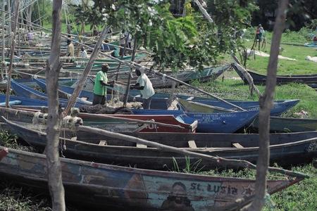 KENYA, KISUMU - MAY 20, 2017: Two african man preparing his boat before work. People taking shower in the lake. Redakční