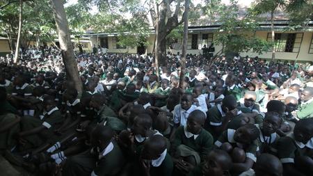 KENYA, KISUMU - MAY 23, 2017: Big crowd of African children in uniform sitting on a ground outside near school.