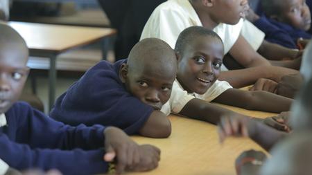 KENYA, KISUMU - MAY 23, 2017: Close-up view of three african boys in uniform sitting in classroom in school Redakční