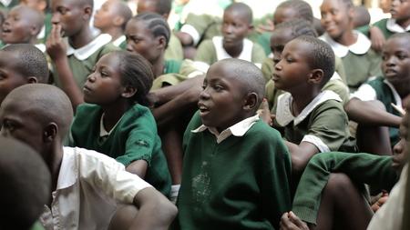 KENYA, KISUMU - MAY 23, 2017: Group of African children in green uniform sitting on ground, smiling, talking. Redakční