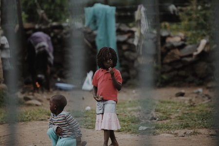 KENYA, KISUMU - MAY 20, 2017: View through the fence. Group of african people spending time outside. Little girl having fun.