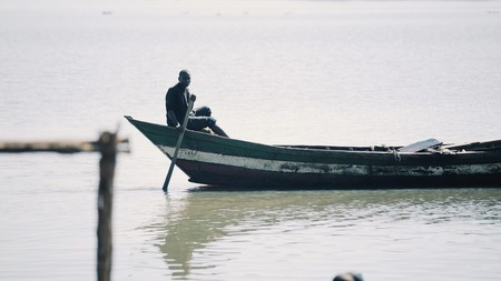 KENYA, KISUMU - MAY 20, 2017: Young african man, fisherman sitting in the boat alone and rowing in the sea.