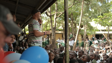 KENYA, KISUMU - MAY 23, 2017: Caucasian men standing and talking in African school to group of children.