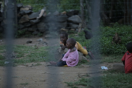 KENYA, KISUMU - MAY 23, 2017: View through the fence. Group of african people spending time outside. Little kids having fun.