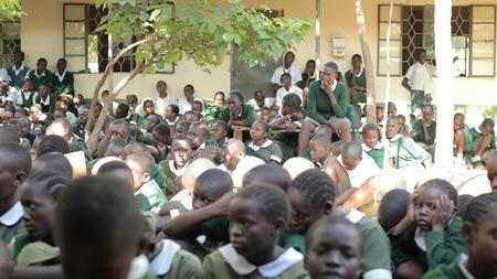 KENYA, KISUMU - MAY 23, 2017: African children in uniform sitting on ground, listen and starting laughing.