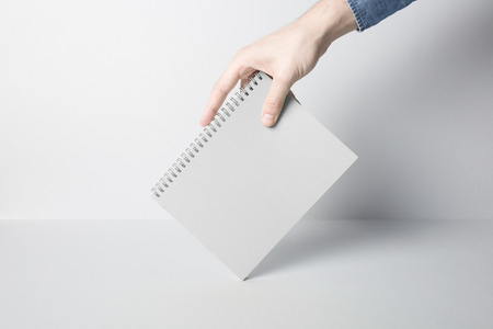 Hands holding blank cover of wire binding notebook