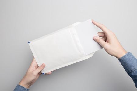 Hand holding lege opgevulde envelop Mock-up, klaar om uw ontwerp te vervangen.