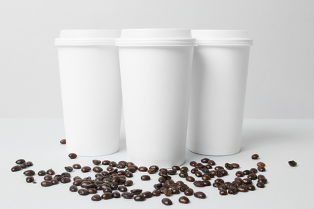 White paper cups with coffee beans
