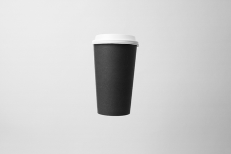 Blank black paper cup with white cap in the air Banco de Imagens