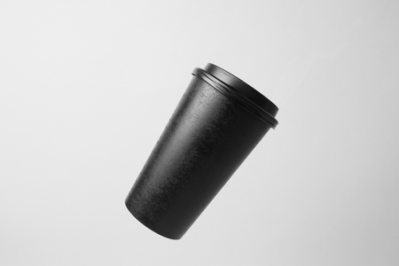 Blank black paper cup in the air
