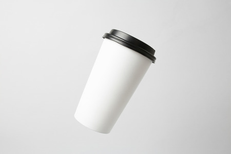 Blank white paper cup with a black cap in the air