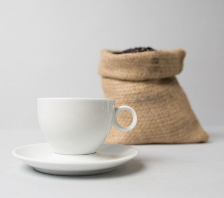 Coffee cup with a brown knitted coffee sack Banco de Imagens