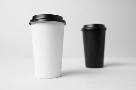 Black and white paper cup with a black capmockup