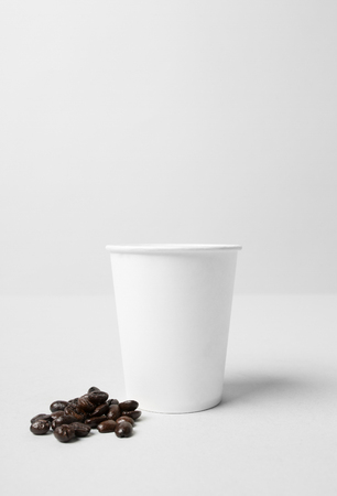 White paper cup with coffee beans