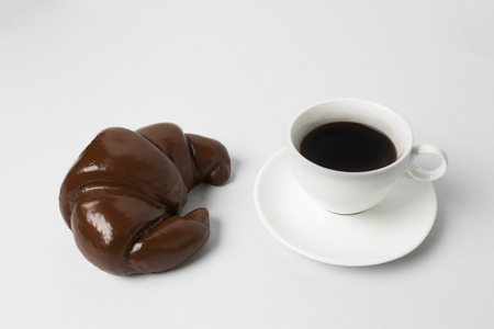 Coffee cup with a chocolate croissant Banco de Imagens
