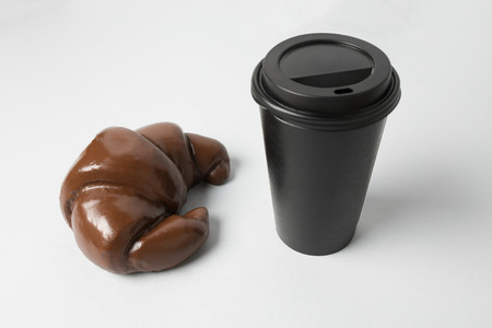 Black paper cup with a chocolate croissant Banco de Imagens