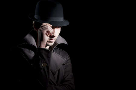 private investigator: man dressed in a trench with a hat on his head isolated on black