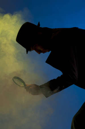 private investigator: Private detective searching for information, shooted in studio on a blue background with yellow light and smoke Stock Photo