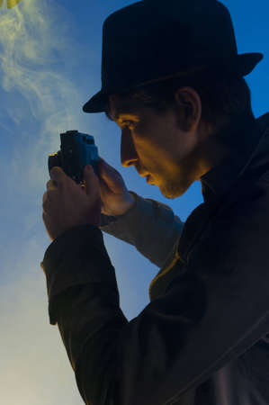 Private detective taking pictures with a small camera, shooted in studio on a blue background with yellow light and smoke
