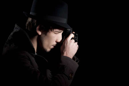 Private detective taking pictures with a small camera, isolated in black photo
