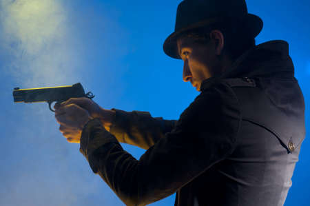 Man holding a gun, shooted in studio on a blue background with yellow light and smoke Stock Photo - 8655012