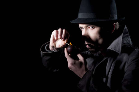 spy glass: Private detective lighting his pipe, isolated on a black background Stock Photo