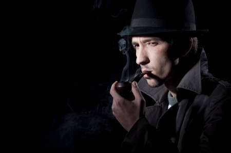private detective smoking a pipe, isolated on a black background Stock Photo - 8654992