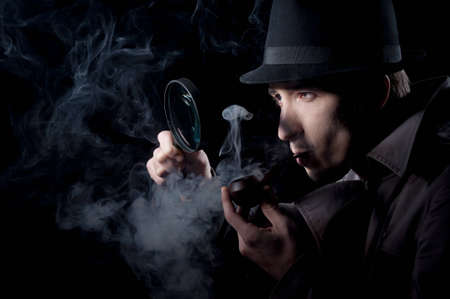 Private detective searching for information, isolated on a black background photo