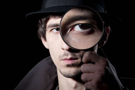 trench: Private detective watching through a magnifying glass, isolated on a black background