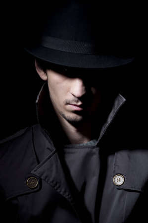 fedora hat: young criminal in shadow, isolated on a black background