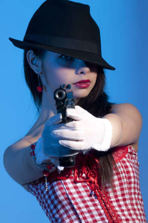 young girl dressed elegant holding a gun photo