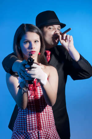 young couple dressed elegant playing as bonnie and clyde Stock Photo