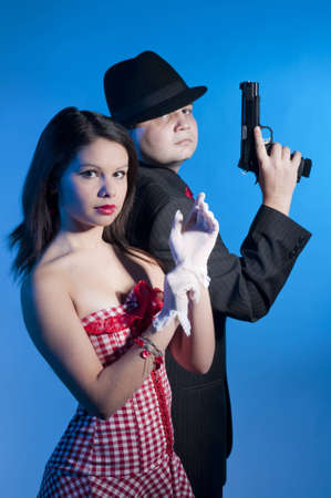 young couple dressed elegant playing as bonnie and clyde photo