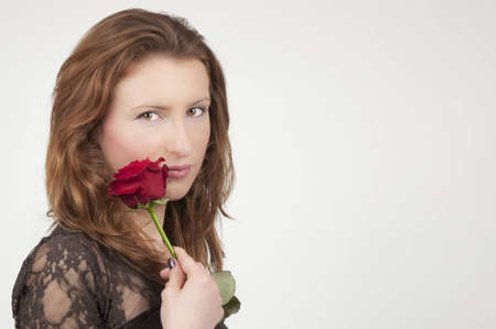 young girl playing with a red rose recived for valentine's day; isolated on a white background photo