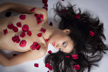 beautiful suntanned female body in petals of scarlet roses Stock Photo - 8855354