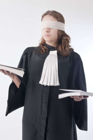 female lawyer: Young law school student holding statute books blindfolded with a scarf
