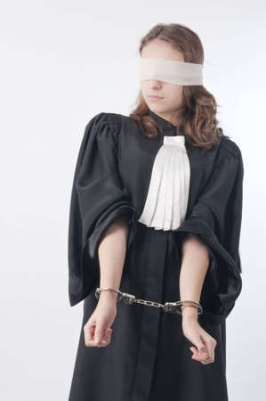 Young law school student holding statute books blindfolded and handcuffed photo