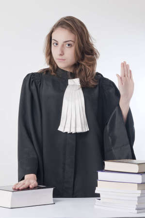 statute: Young law school student holding her hand on to the statute book and swearing