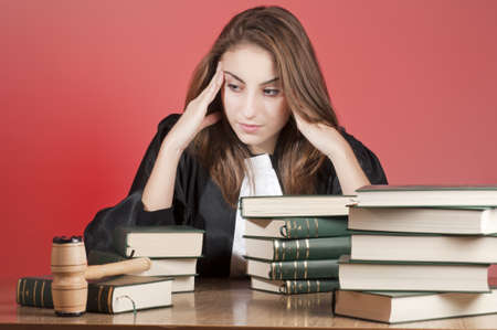 Concentrated young law school student surrounded by statute books photo