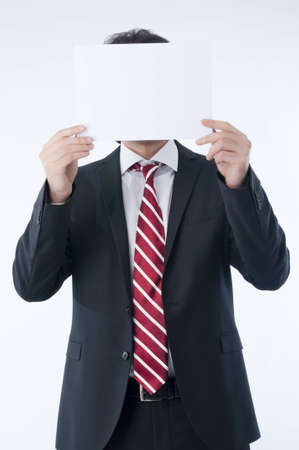 holding paper: Businessman holding an empty advert in front of his face Stock Photo