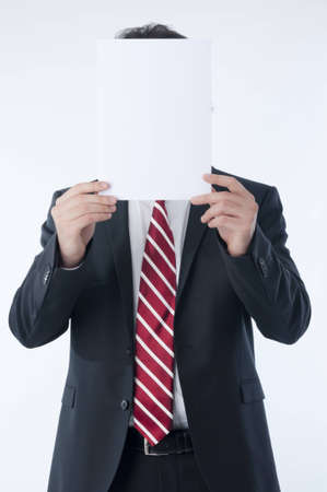 advert: Businessman holding an empty advert in front of his face Stock Photo