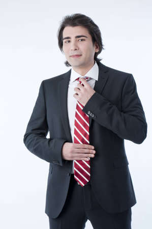 Confident young business man arranging his tie