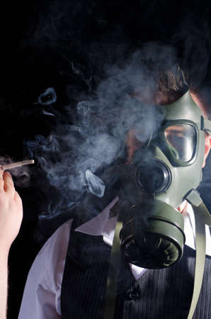 Man wearing a gas mask for protection against cigarette smoke Stock Photo